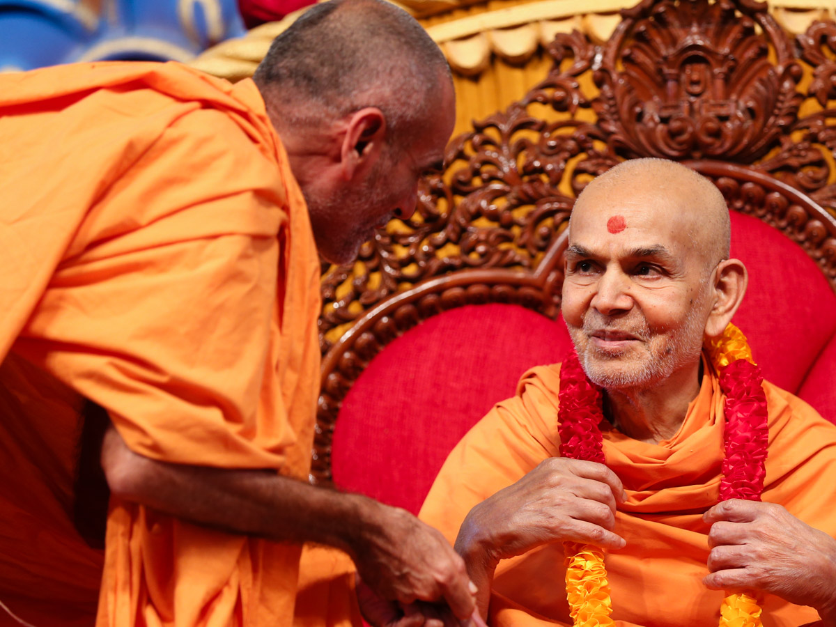 Pujya Anandswarup Swami honors Swamishri with a garland