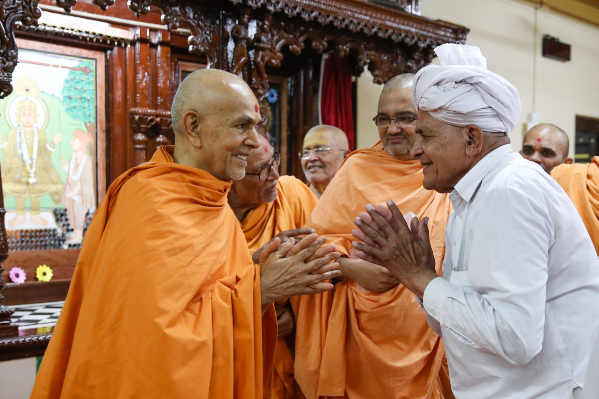 Swamishri converses with a devotee
