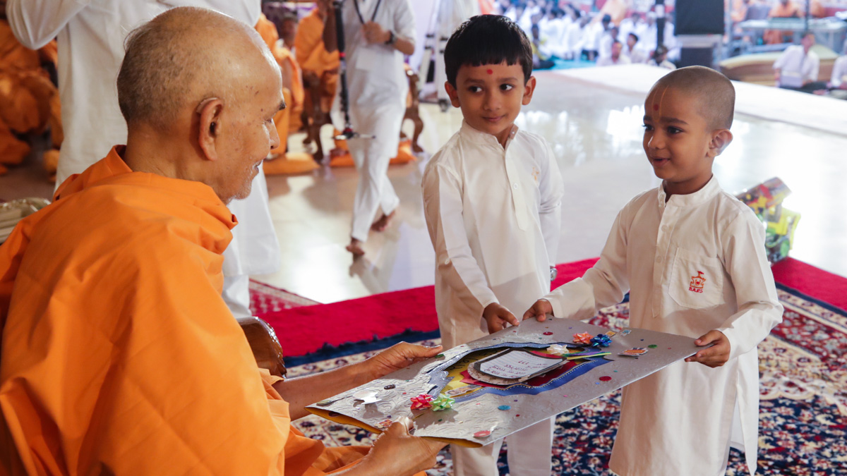 Children present an invitation to Swamishri for the evening Bal Din program