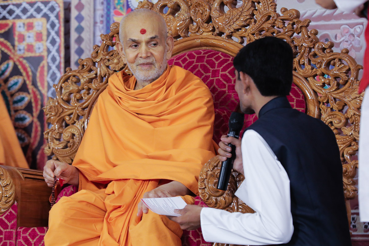 Swamishri interacts with a youth