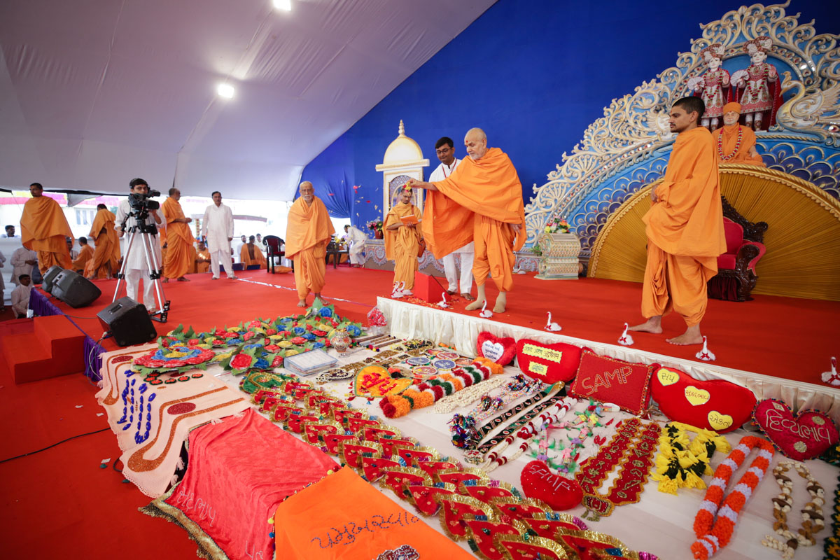 Swamishri sanctifies shawls and garlands by showering flower petals