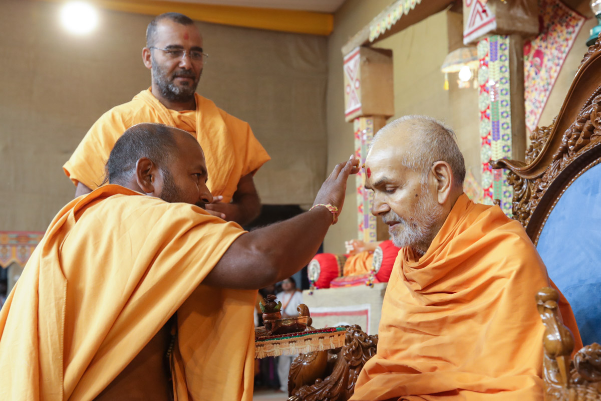 A sadhu applies archa to Swamishri