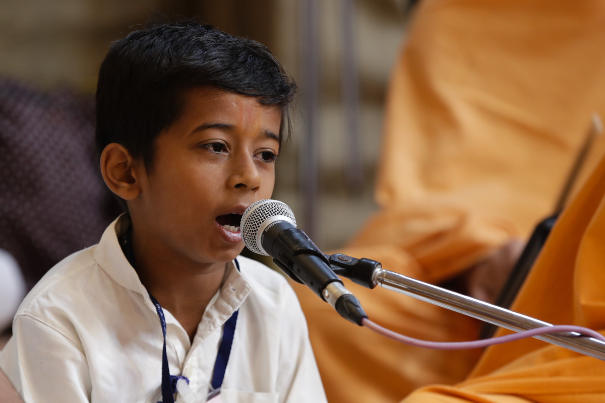 A child sings a kirtan in Swamishri's puja