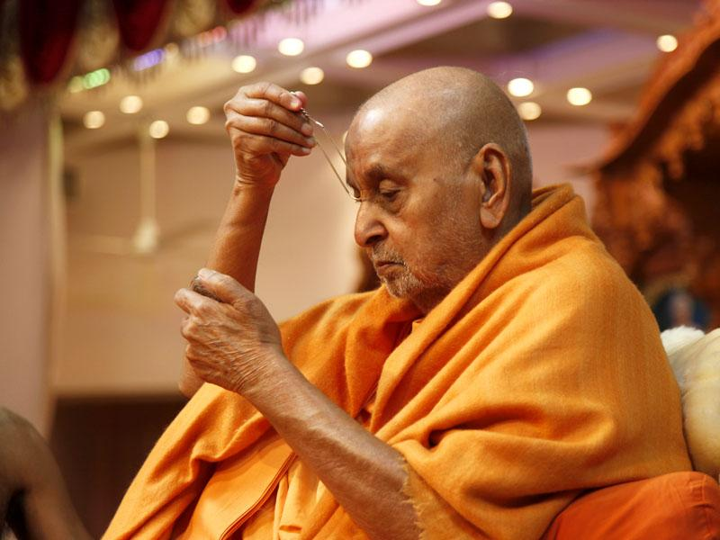 During his morning puja, Swamishri applies tilak...