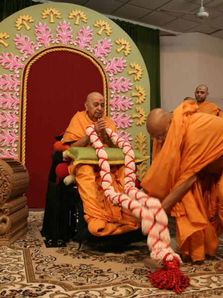Pujya Ishwarcharan Swami welcomes Swamishri with a garland