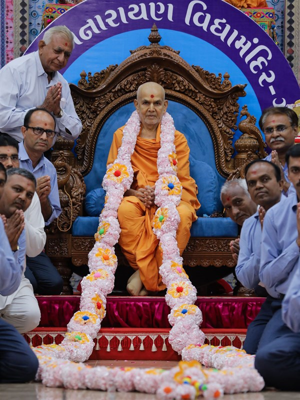 Vidyamandir teachers honor Swamishri with a garland