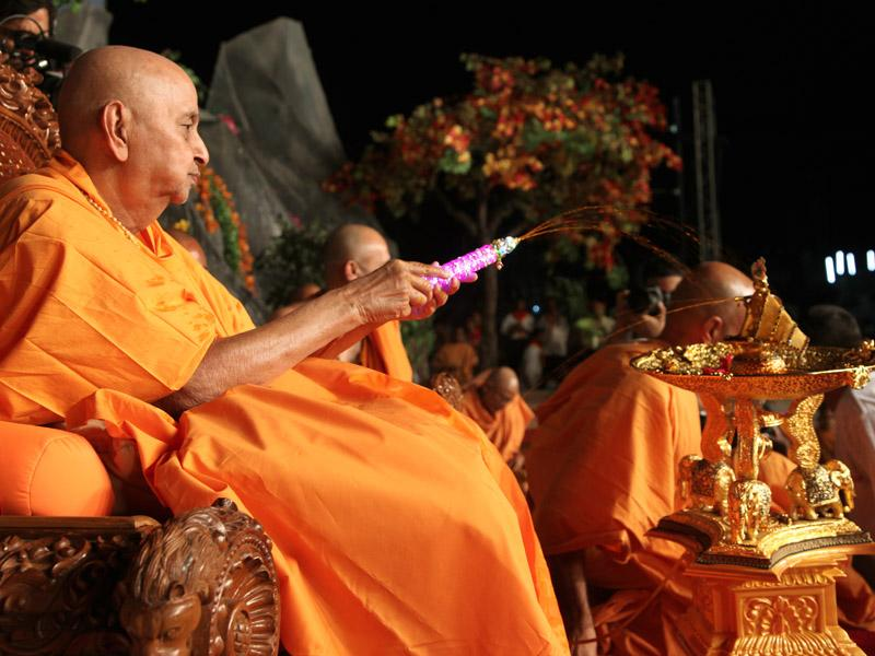 Swamishri first showers fragrant colored water on Shri Harikrishna Maharaj