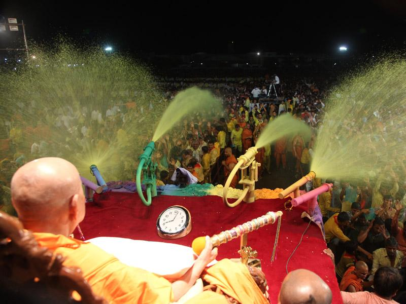 Swamishri showers sanctified colored water on devotees
