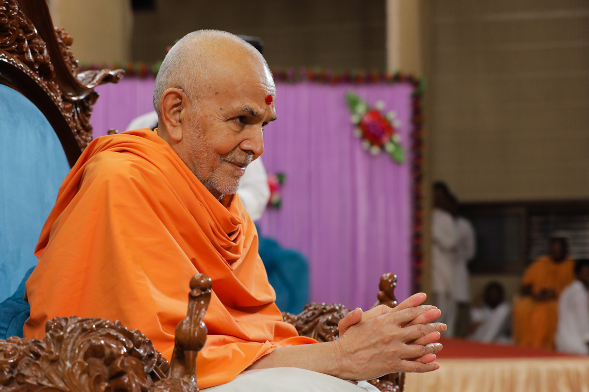 Swamishri blesses devotees as they pass by during samip darshan