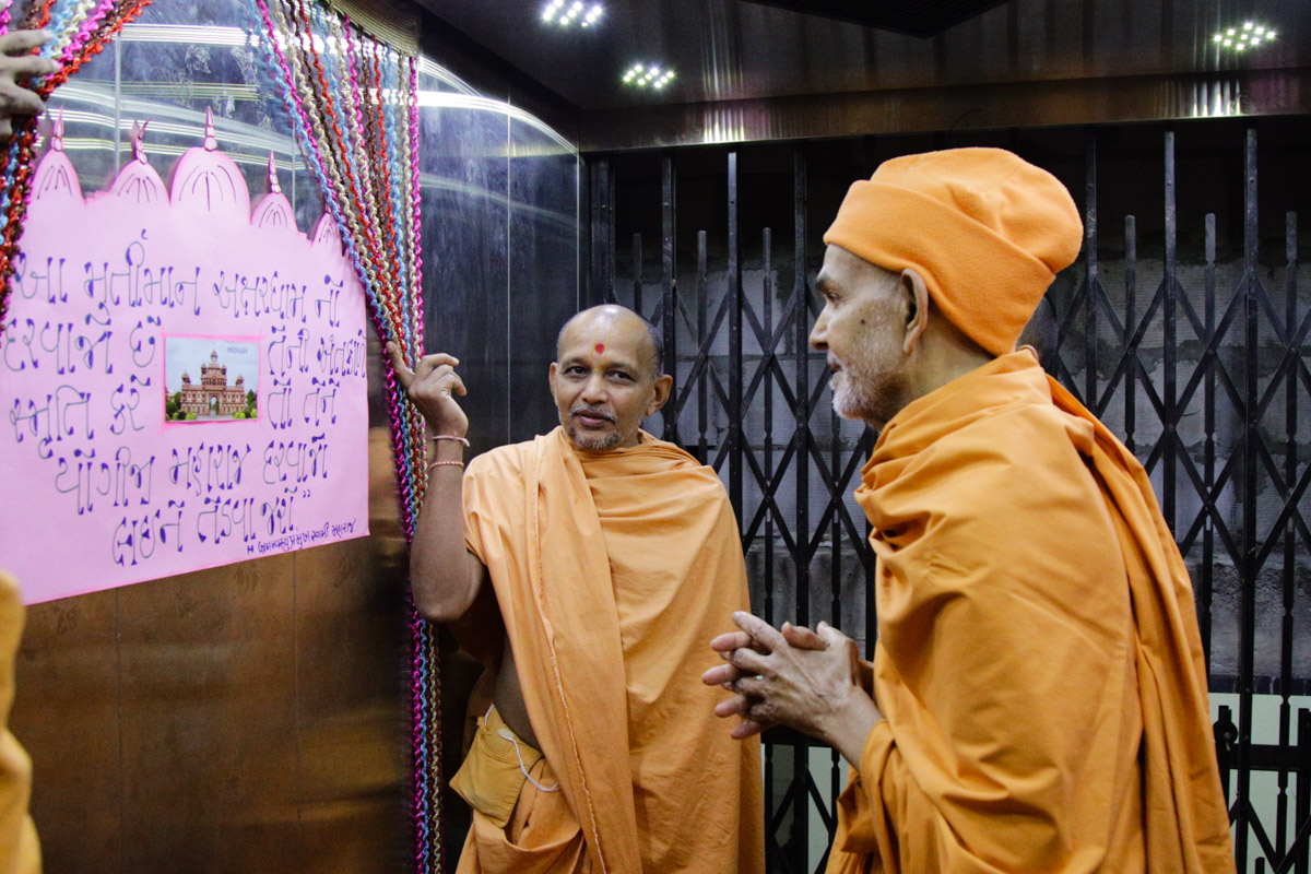 Swamishri observes a display in the lift