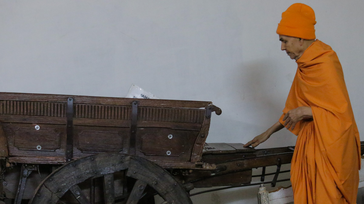 Swamishri engrossed in the darshan of a cart sanctified by Brahmaswarup Shastriji Maharaj