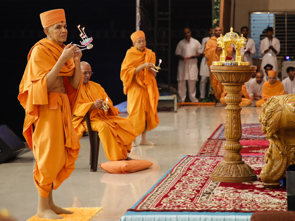 Swamishri, Pujya Doctor Swami and Pujya Tyagvallabh Swami perform the evening arti
