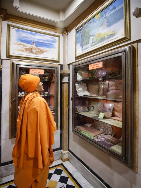 Swamishri observes an exhibition display in the abhishek mandap