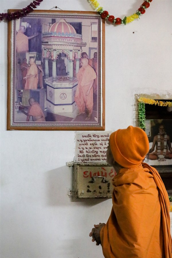 Swamishri observes a photo at the shrine of Purushottamdas Swami (Khandeshi)