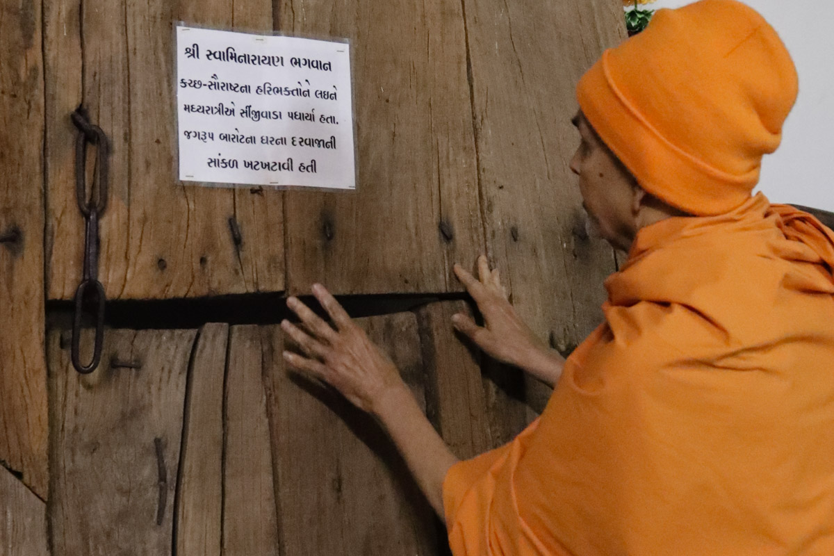 Swamishri reverentially touches the door of Jagrup Barot's house in Sinjiwada (Kutch) sanctified by Bhagwan Swaminarayan
