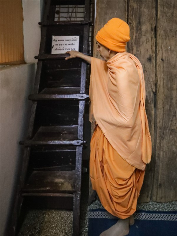 Swamishri reverentially touches a ladder sanctified by Bhagwan Swaminarayan in Dabhan