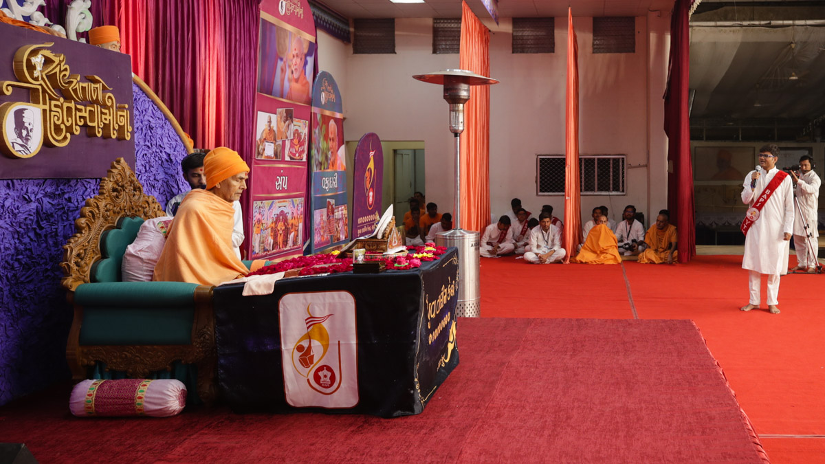 A youth of the Yuva Talim Kendra, Sarangpur, presents mukhpath before Swamishri