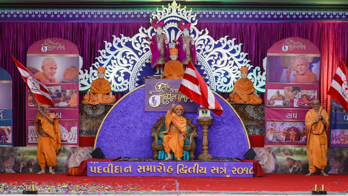 Swamishri, Pujya Tyagvallabh Swami and Atmaswarup Swami wave BAPS flags