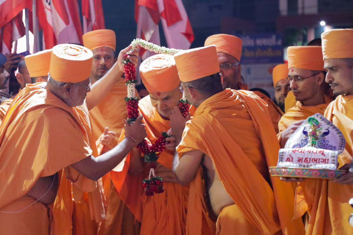 On arrival, Brahmatirth Swami and Apurvamuni Swami welcome Param Pujya Mahant Swami Maharaj with a garland