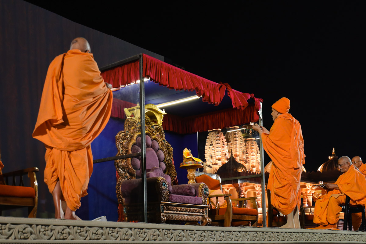 Swamishri and senior sadhus perform the evening arti