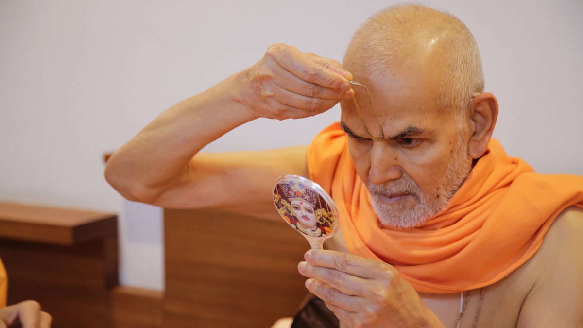 Param Pujya Mahant Swami Maharaj applies tilak on his forehead