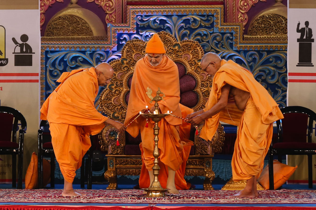 "Swamishri and senior sadhus light the inaugural lamp for Bal & Yuva Adhiveshan 2019<br><a href=""https://www.baps.org/Photos/2018/9-December-2018-17597.aspx?mid=152693"" target=""blank"" style=""text-decoration:underline; color:blue;"">For more photos</a>"