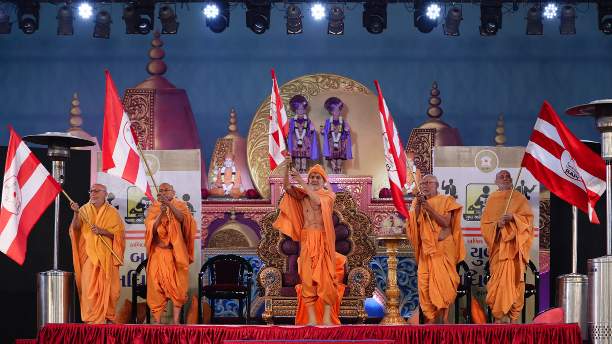 Swamishri and senior sadhus wave the BAPS flags