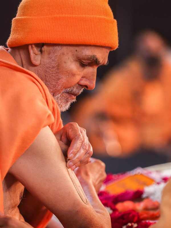 Swamishri applies tilak on his upper arms