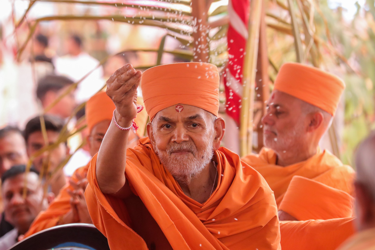 Swamishri blesses all by showering rice grains