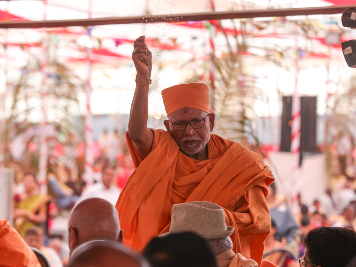 Pujya Bhaktipriya Swami (Kothari Swami) blesses devotees by showering rice grains