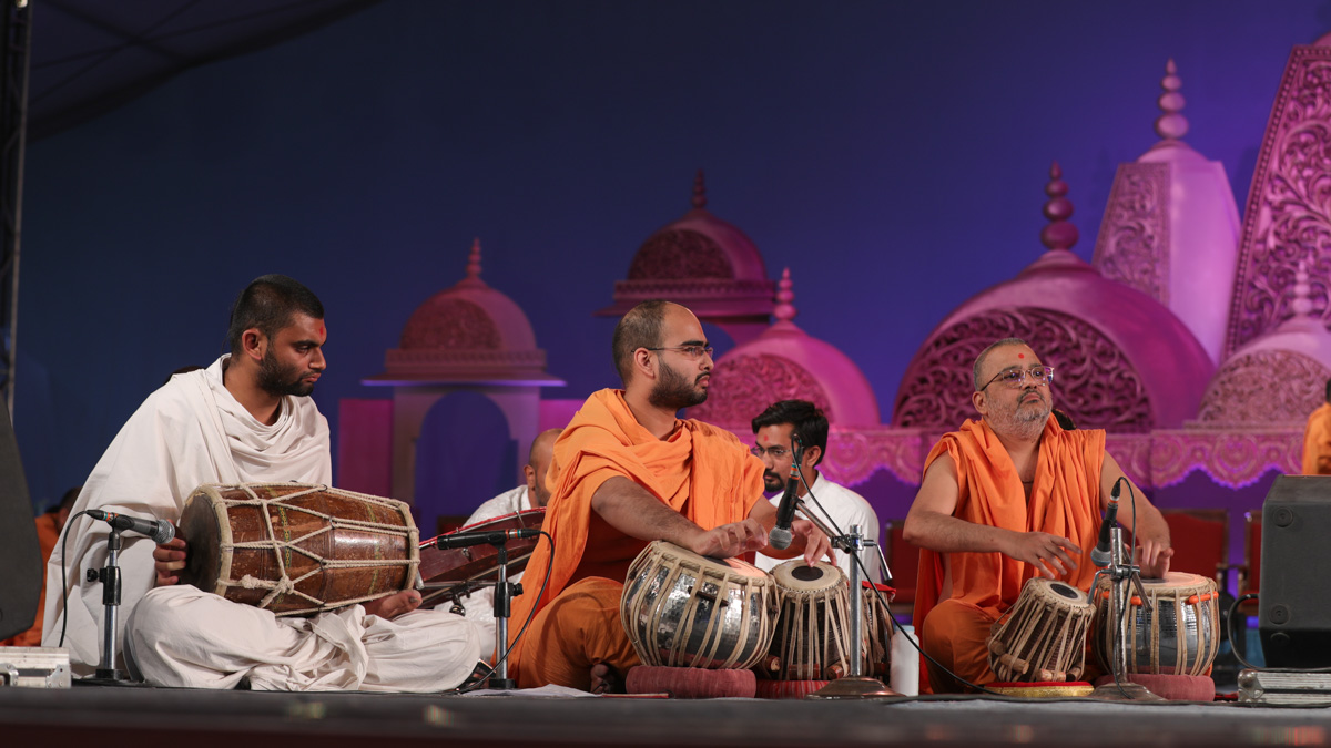 Sadhus and a parshad play musical instruments