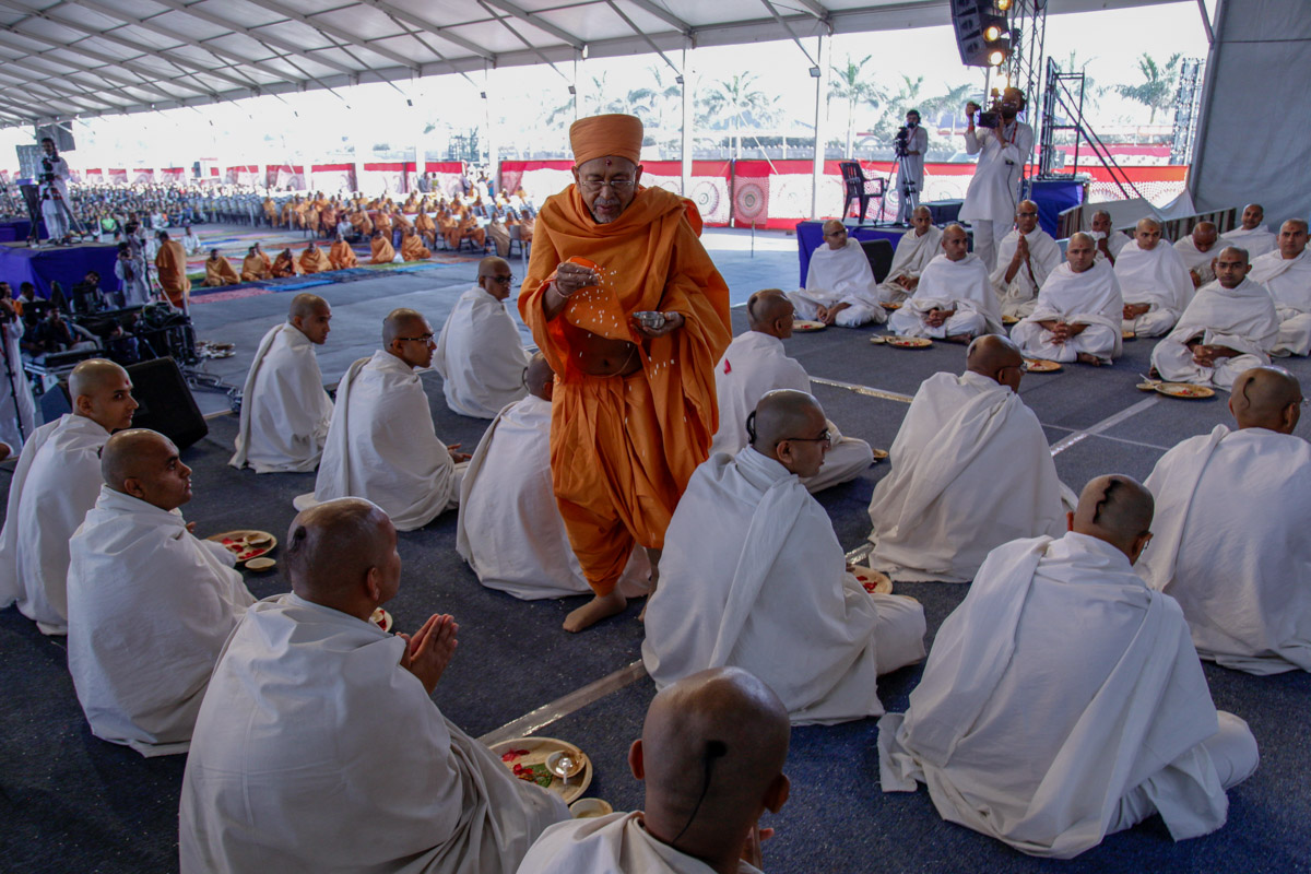 Pujya Tyagvallabh Swami blesses parshads by showering rice grains