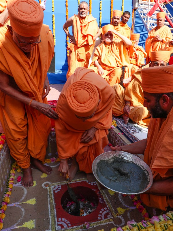 Swamishri pours cement in the pit