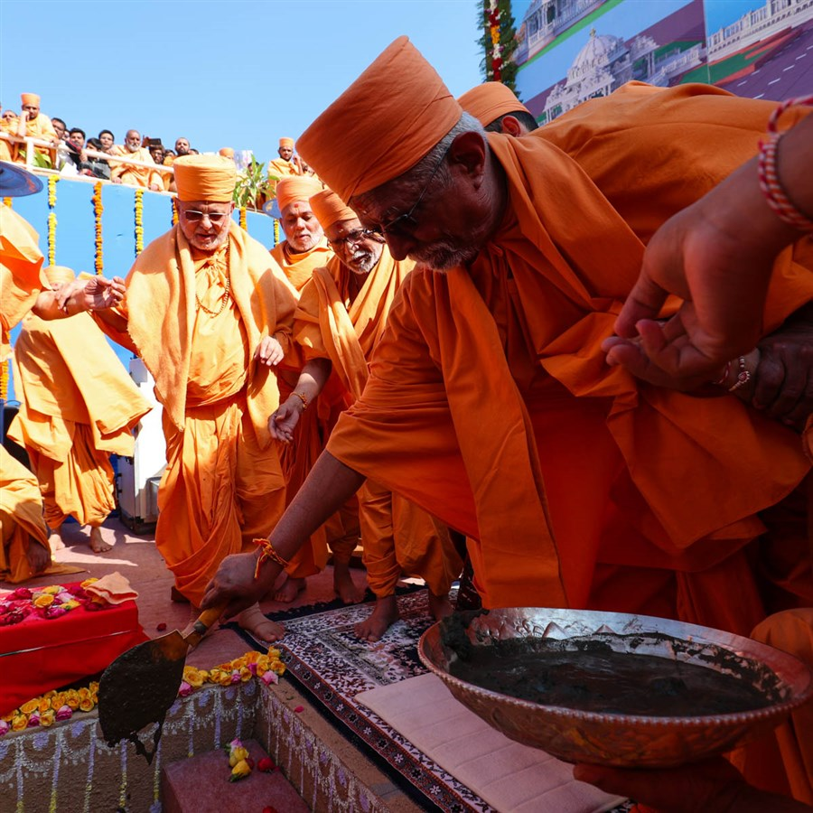 Pujya Swayamprakash Swami (Doctor Swami) pours cement in the foundation pit