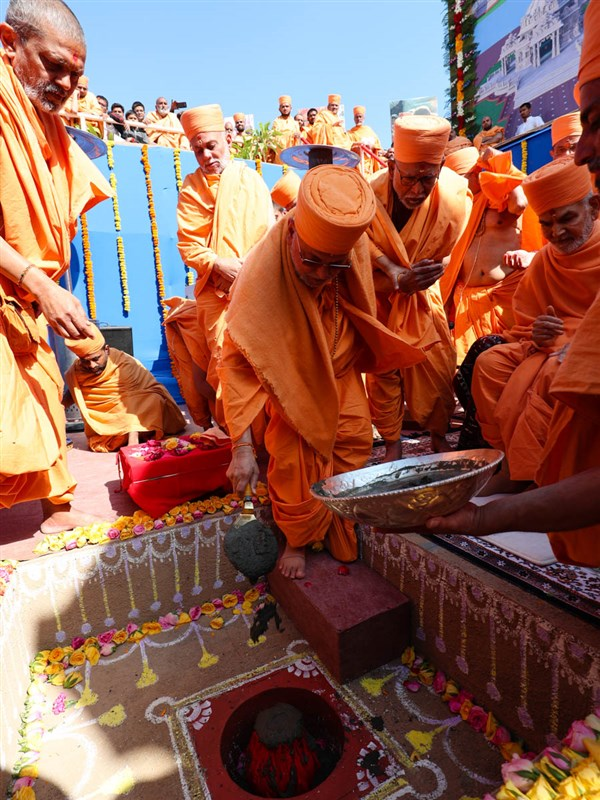 Pujya Ishwarcharan Swami pours cement in the foundation pit