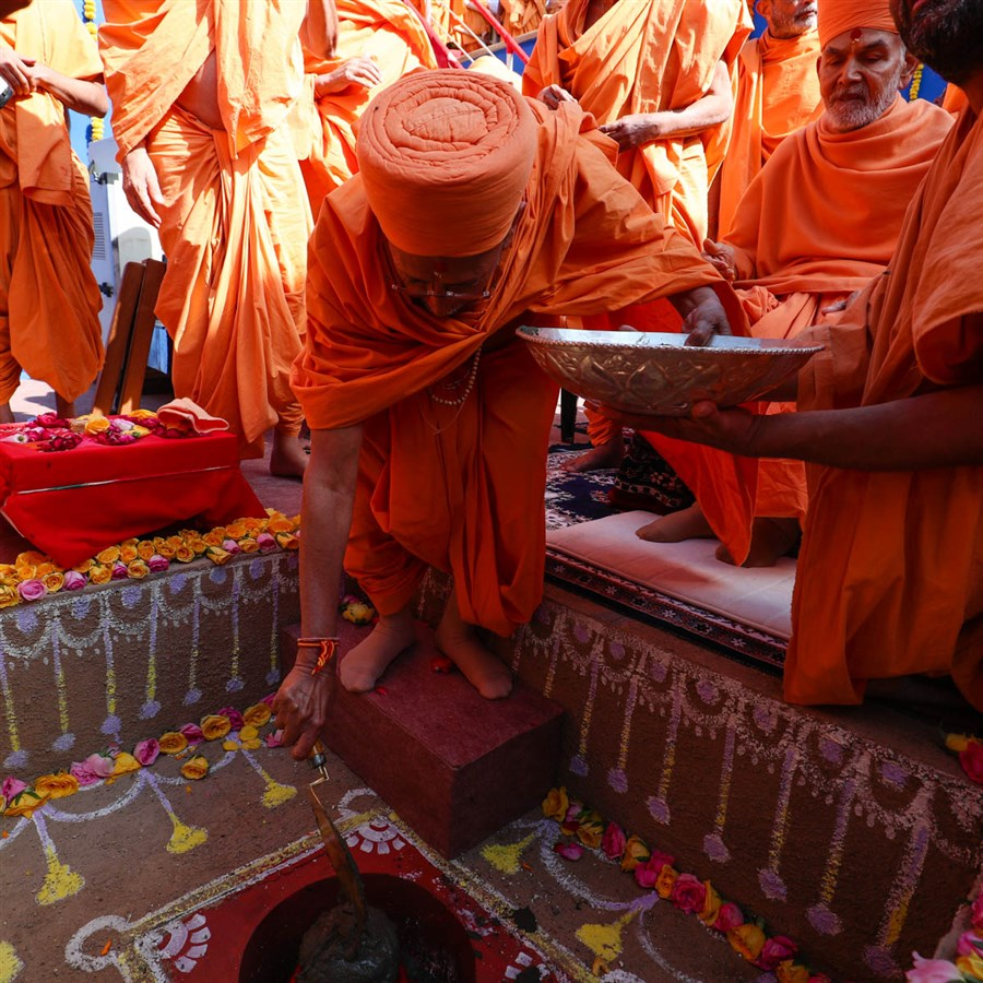 Pujya Tyagvallabh Swami pours cement in the foundation pit