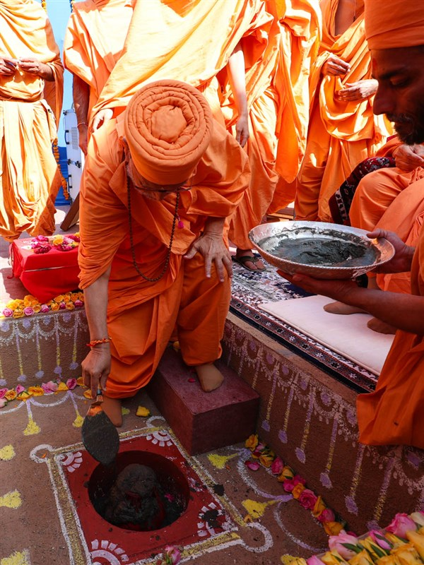 Pujya Ghanshyamcharan Swami pours cement in the foundation pit