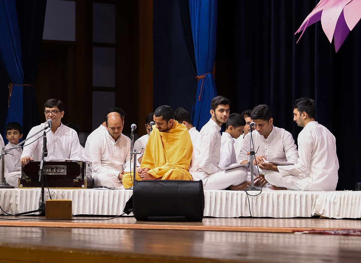 Sadhus and youths present a kirtan aradhana in the evening satsang assembly