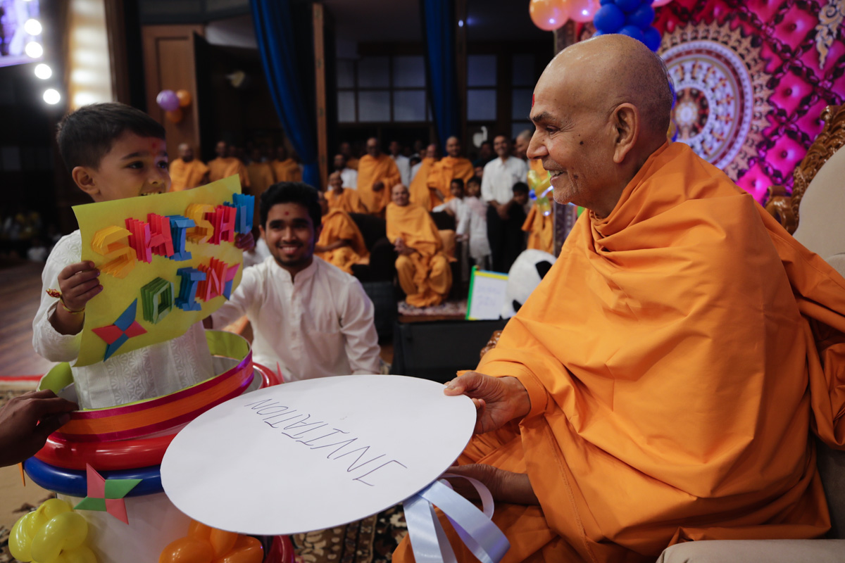 A child invites Swamishri to the evening Shishu Din assembly
