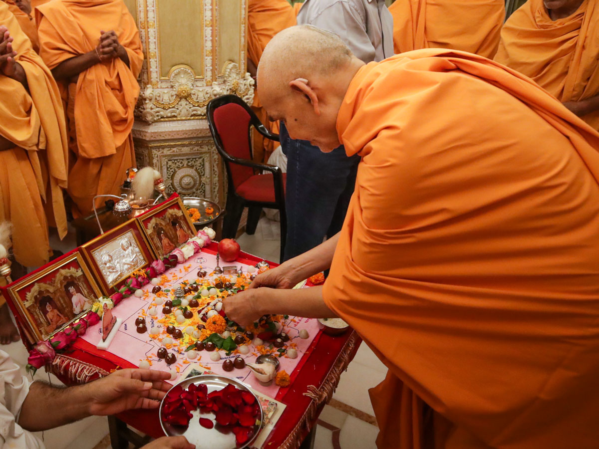 Swamishri offers mantra-pushpanjali during the morning mahapuja