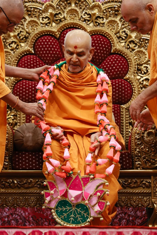 Pujya Kothari Swami and Pujya Viveksagar Swami honor Swamishri with a garland