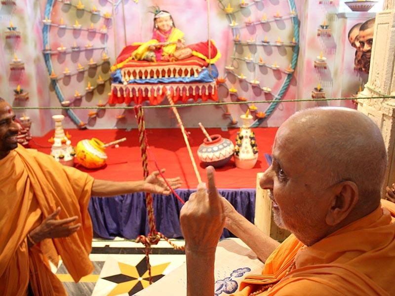 Swamishri swings murti of Shri Krishna in a hindolo