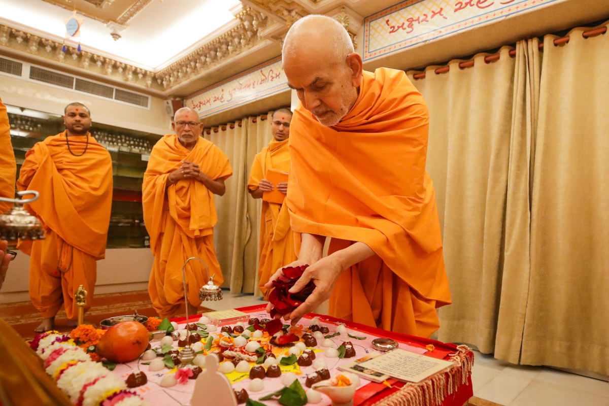 Swamishri offers mantra-pushpanjali in the morning mahapuja