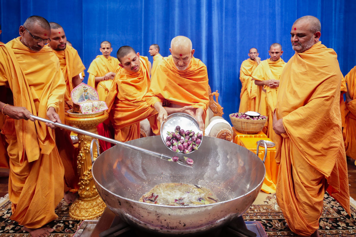 Swamishri adds eggplants (ringna) to the shak mixture in the morning Yuva Karyakar assembly