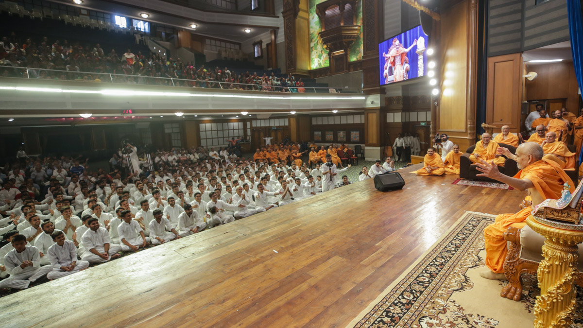 Swamishri makes a gesture to embrace all
