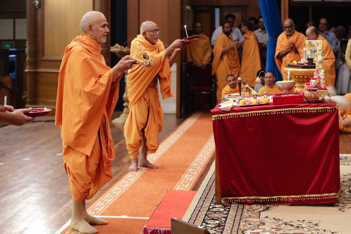 Swamishri and Pujya Bhaktipriya Swami (Kothari Swami) perform the evening arti during the evening assembly