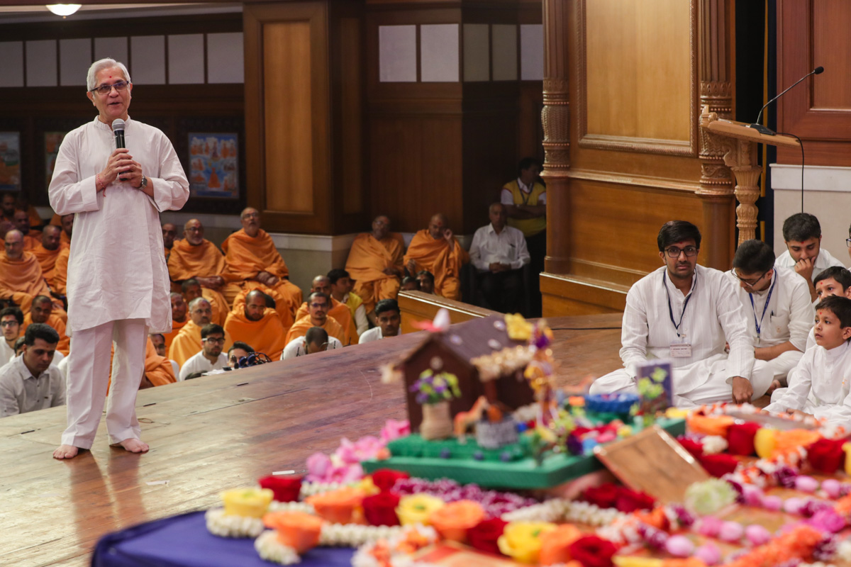 A devotee presents mukhpath before Swamishri