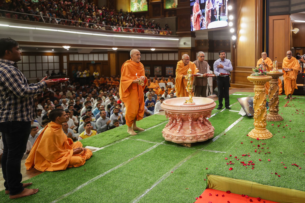 Swamishri, Pujya Bhaktipriya Swami (Kothari Swami) and invited guests perform the evening arti