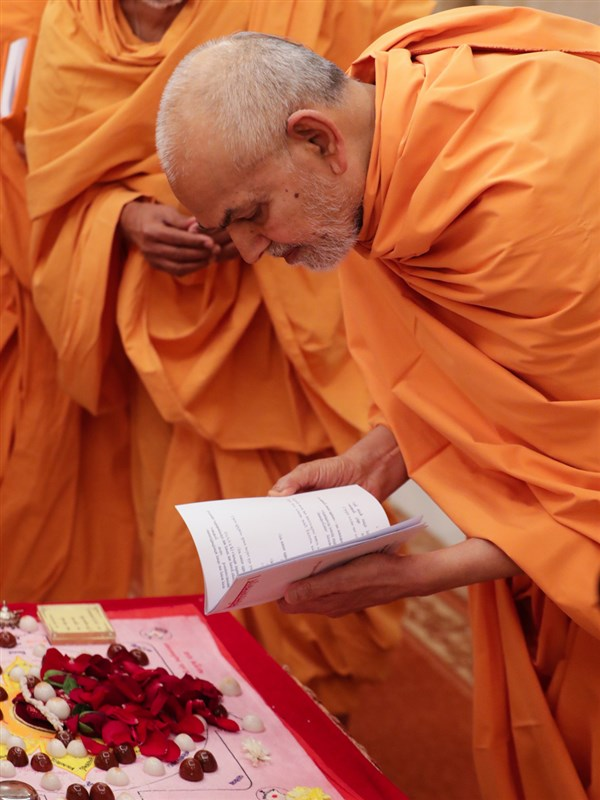 Swamishri looks at the mahapuja booklet