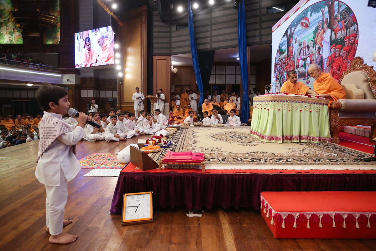 A child presents mukhpath before Swamishri